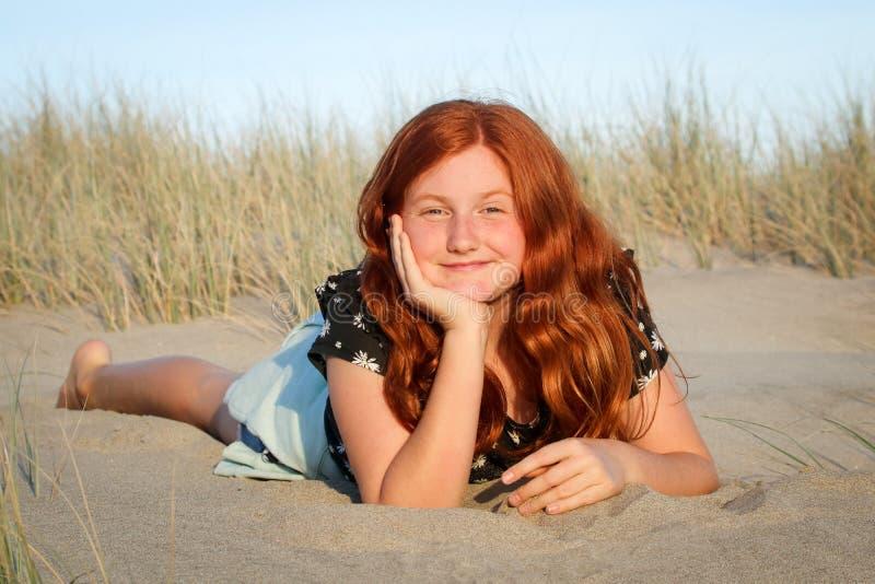 Rood haired meisje die op een wit zandig strand van Nieuw Zeeland liggen royalty-vrije stock afbeeldingen