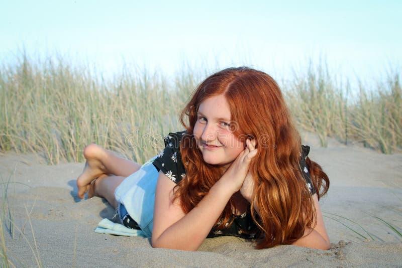 Rood haired meisje die op een wit zandig strand van Nieuw Zeeland liggen stock fotografie