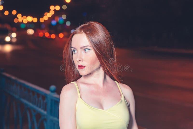 Rood haired meisje, portret in nachtstad het plaatsen De stijlportret van de straatmanier van jonge vrij mooie vrouw met lang royalty-vrije stock foto