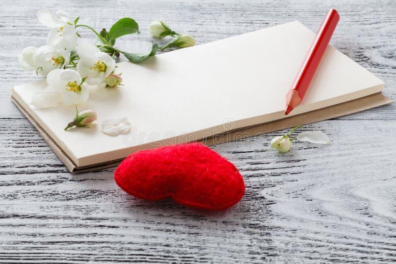 Rood hart, bloeiende twijg, giftkaart, rond twijgen van bloeiende amandelen op houten achtergrond stock foto's