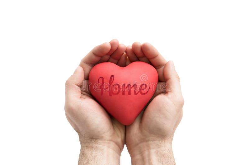 Rood hart met gestempeld huiswoord in mensen` s handen stock foto