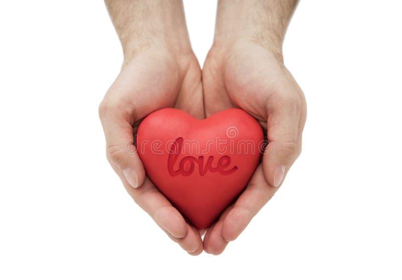 Rood hart met gestempeld liefdewoord in mensen` s handen royalty-vrije stock foto