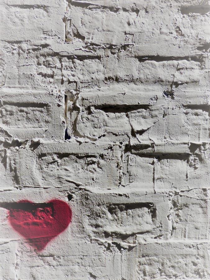 Rood hart op een witte bakstenen muur - 2 - linksonder royalty-vrije stock afbeeldingen