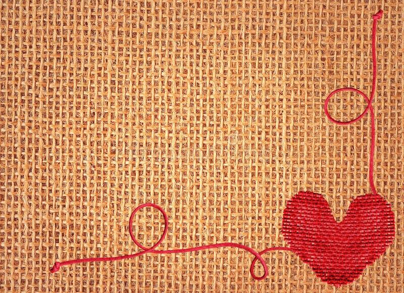 Rood hart over de achtergrond van de linnentextuur royalty-vrije stock afbeeldingen