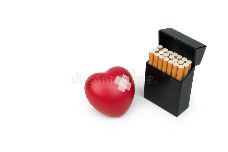 Rood hartsymbool met hechtpleister en het sigaretpak stock afbeelding