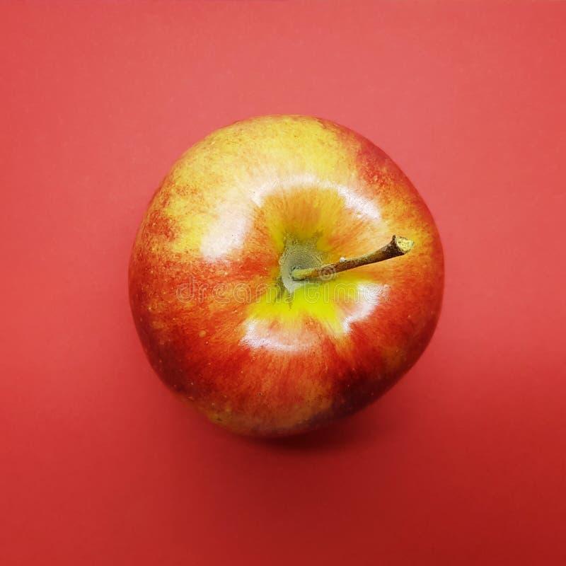 Rood - heerlijke appel over rode achtergrond Gezonde appelen stock afbeeldingen