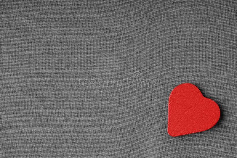 Rood houten decoratief hart op grijze grijze doekachtergrond. stock afbeelding