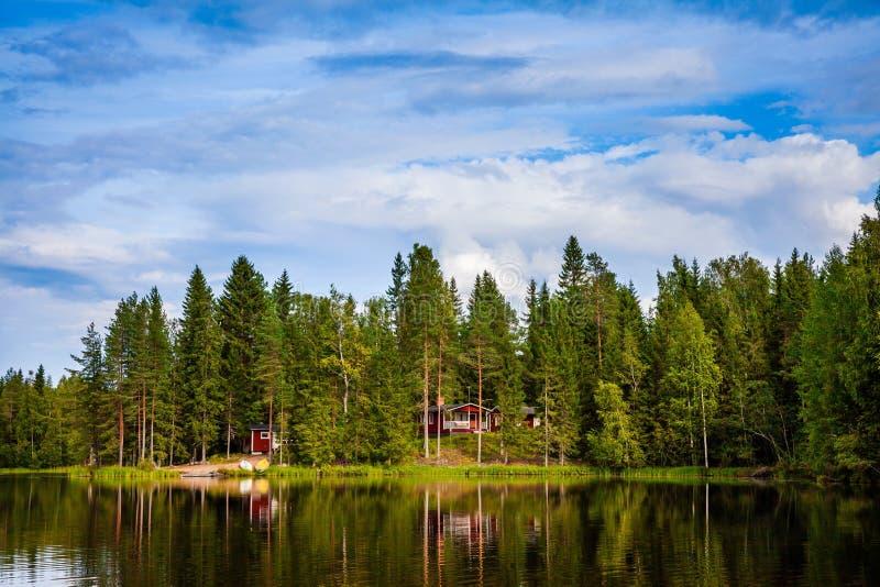 Rood houten plattelandshuisje door het meer stock afbeeldingen