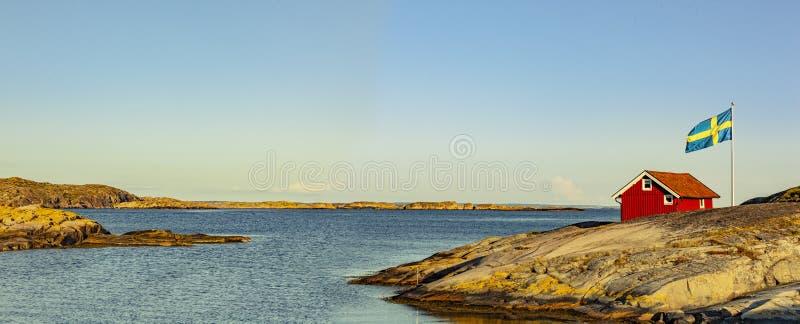 Rood huis in Zweden bij de skerry kust stock foto's