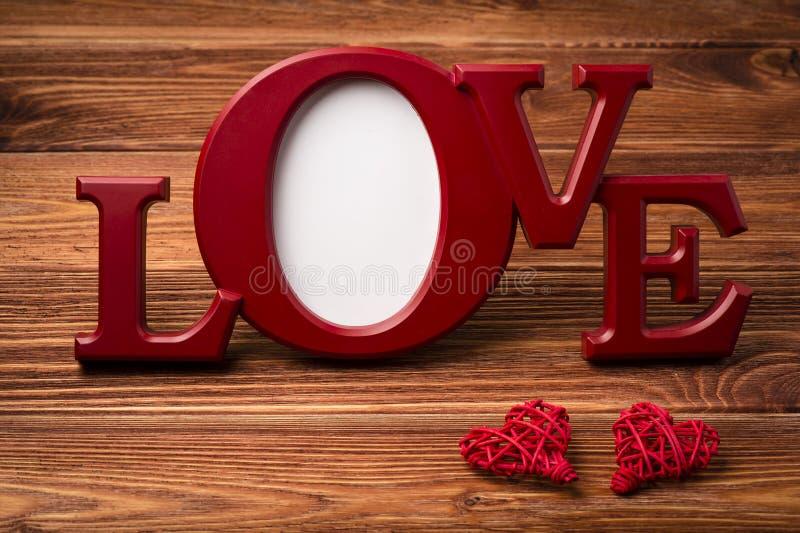Rood kader voor beeldenliefde op de houten achtergrond stock afbeelding