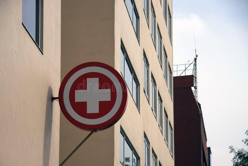Rood Kruiseerste hulp/Medische Signage die [Teken] van kant van een gebouw hangen stock foto