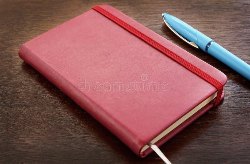 Rood leernotitieboekje met pennen op houten lijst stock afbeeldingen