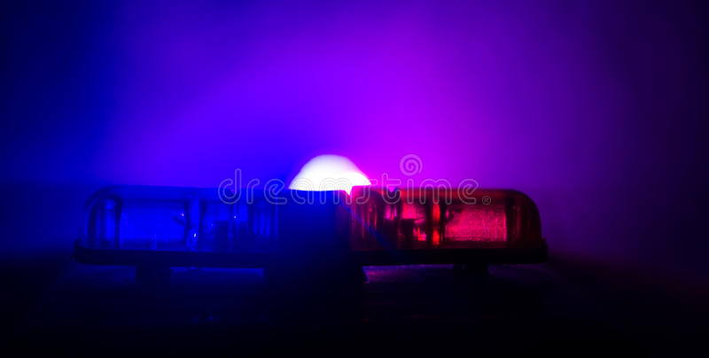 Rood lichtflitser boven op van een politiewagen Stadslichten op de achtergrond Het concept van de politieoverheid stock foto's