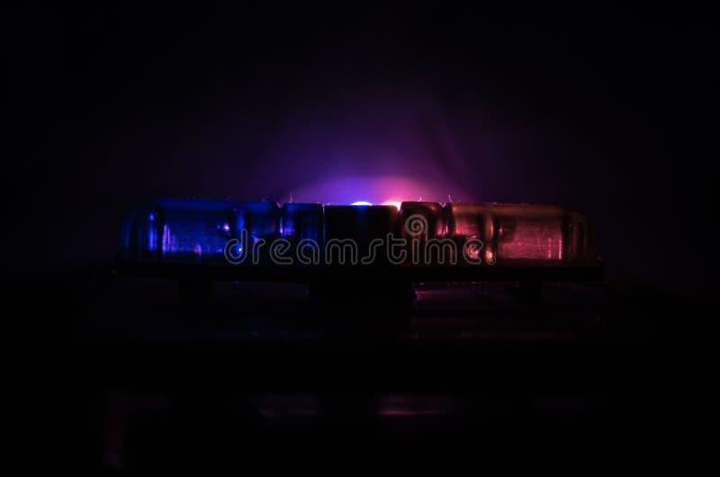 Rood lichtflitser boven op van een politiewagen Stadslichten op de achtergrond Het concept van de politieoverheid stock afbeelding