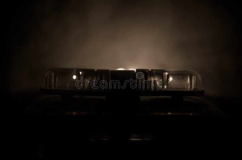 Rood lichtflitser boven op van een politiewagen Stadslichten op de achtergrond Het concept van de politieoverheid stock fotografie
