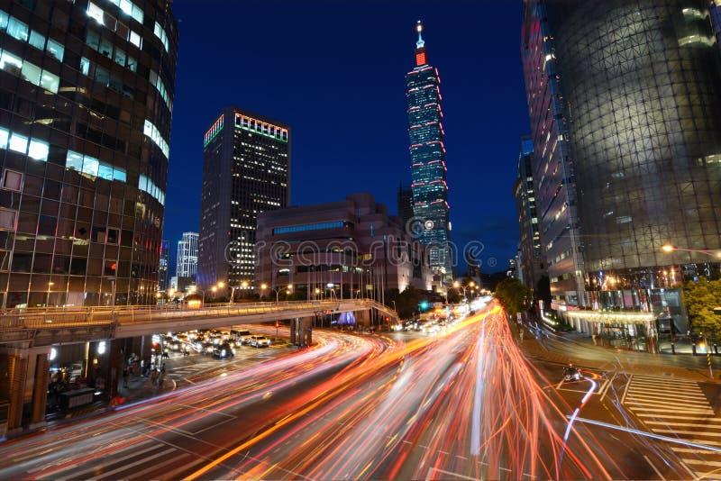 Rood lichtslepen van de strook van het voertuigverkeer over een bezige kruising voor Taipeh 101 stock afbeeldingen