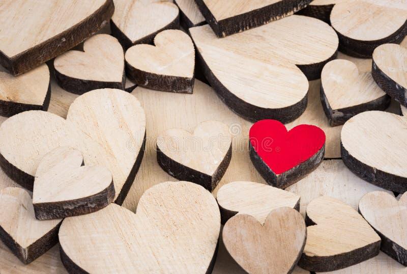Rood liefdehart tussen vele houten harten stock afbeeldingen