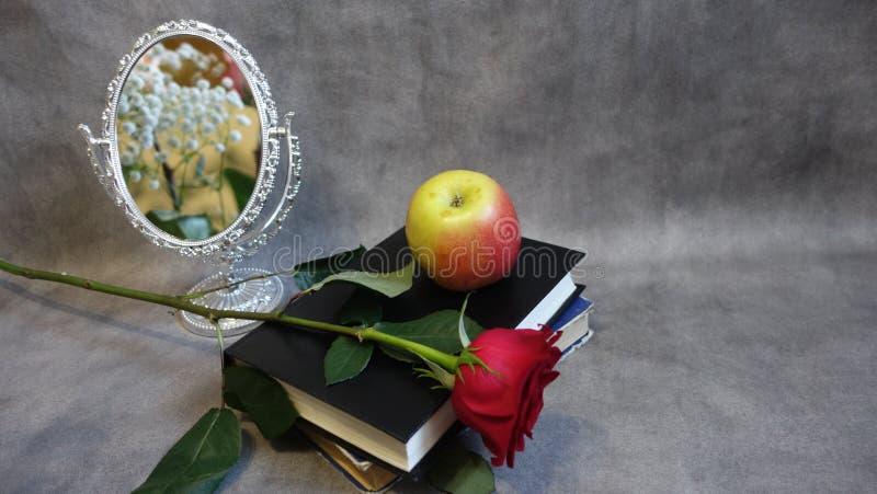 Rood nam en Apple liggend op een boek naast de spiegel toe stock fotografie