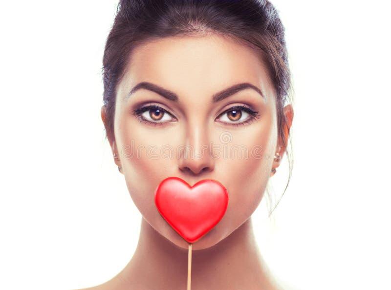 Rood nam toe De schoonheid verraste jong mannequinmeisje met het gevormde koekje van Valentine hart royalty-vrije stock afbeeldingen