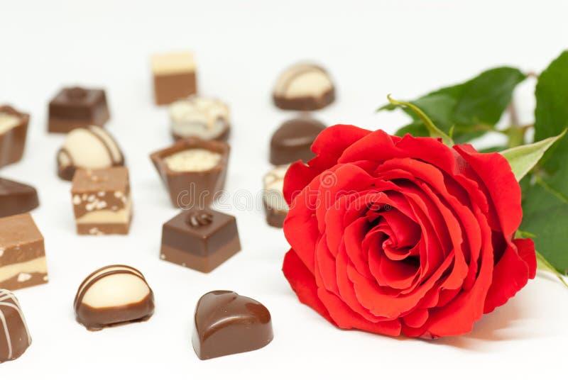Rood nam toe en diverse chocoladevormen op witte achtergrond houden van het Romaanse concept van de valentijnskaart` s dag stock afbeeldingen