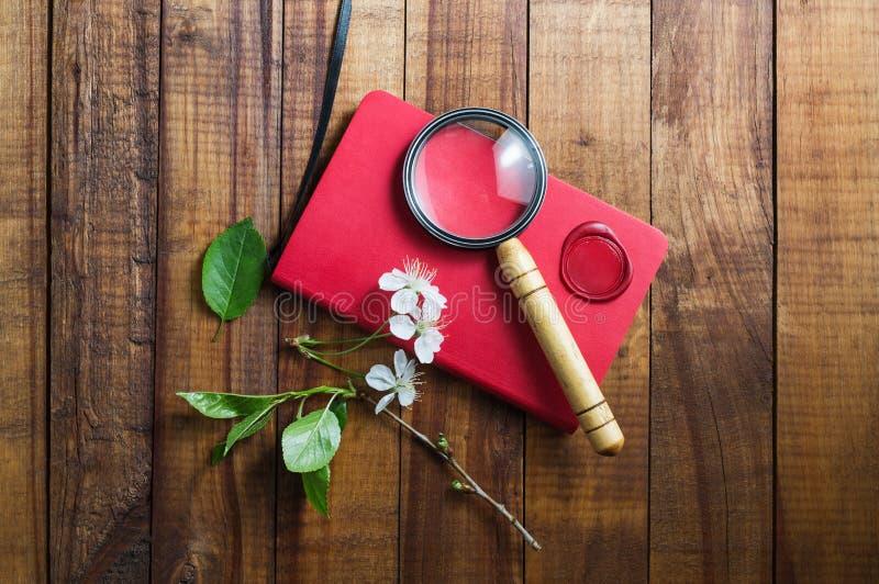 Rood notitieboekje en meer magnifier royalty-vrije stock afbeelding