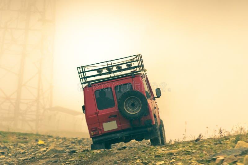 Rood off-road 4x4 voertuig die rotsen beklimmen stock foto