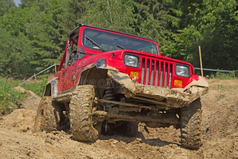 Rood off-road voertuig in modderig terrein. stock afbeelding