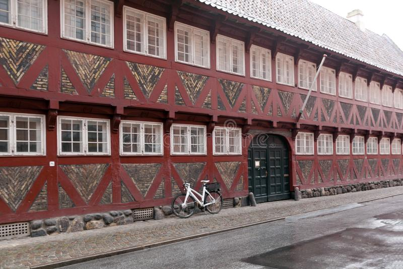 Rood oud huis met witte vensters - helft-betimmerd die huis van hout en bakstenen wordt gemaakt Fiets dichtbij de muur stock foto's