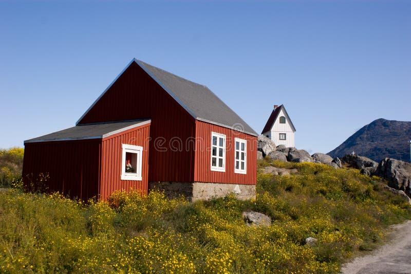 Rood plattelandshuisje in Groenland met witte kerk royalty-vrije stock fotografie