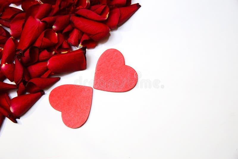 Rood rozenbloemblaadjes en hart stock foto