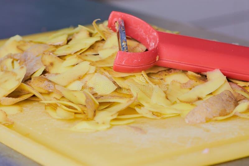 Rood schilmesje op aardappelschillen stock afbeelding
