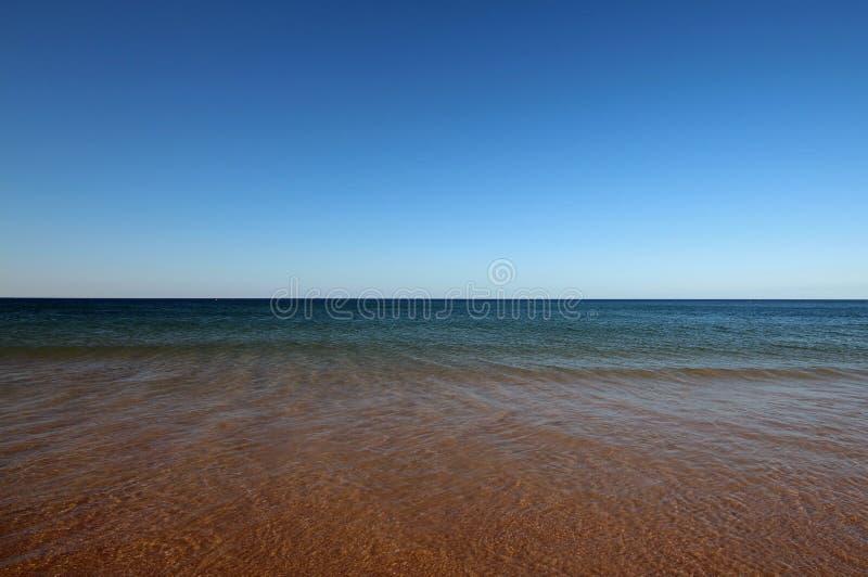 Rood Strand met Turkooise Overzees royalty-vrije stock afbeeldingen