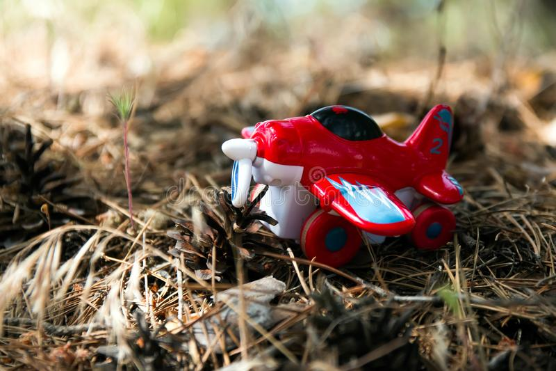 Rood stuk speelgoed vliegtuig tegen, een achtergrond van gebladerte royalty-vrije stock afbeeldingen