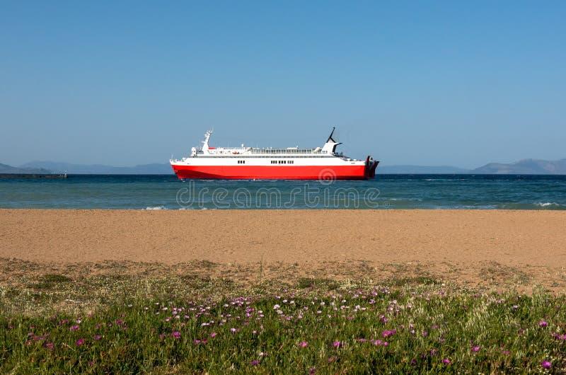 Rood veerboot en strand in Rafina, Griekenland stock foto's