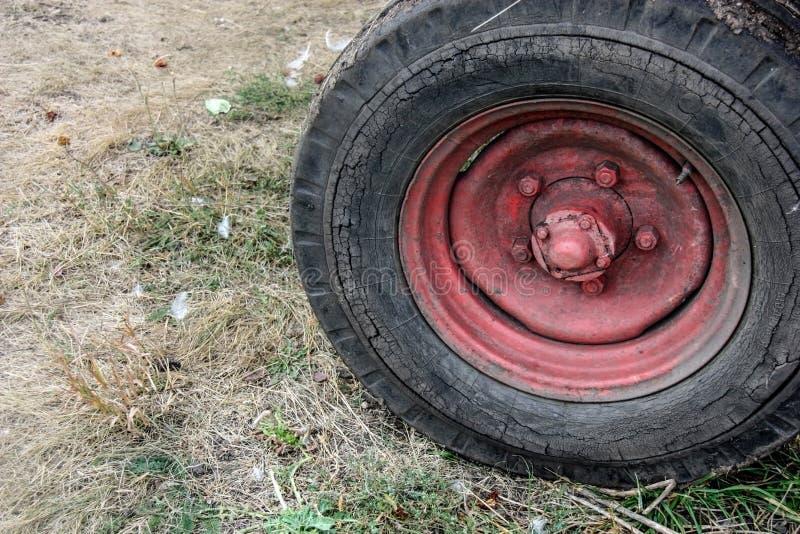 Rood wiel van een oude tractor op de dorpsgrond Autumn Harvest Time royalty-vrije stock afbeelding
