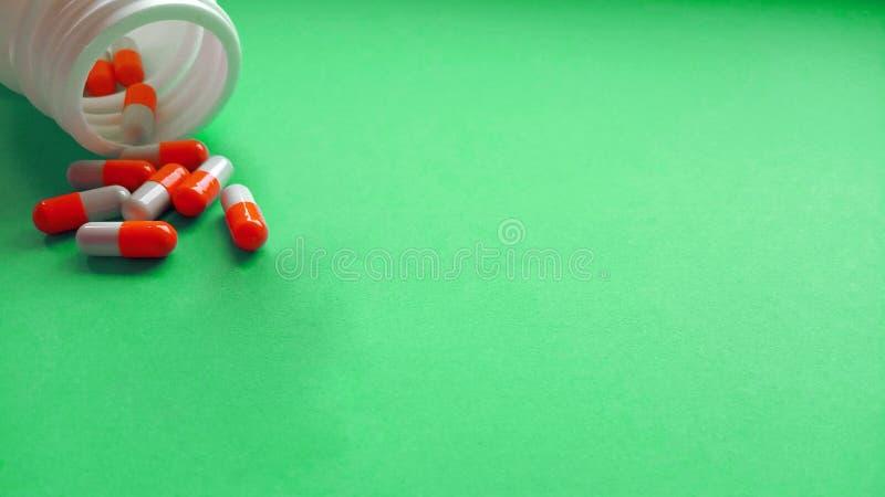 Rood-witte farmaceutische die geneeskundepillen, capsules uit witte plastic drugfles worden uitgespreid op groene achtergrond Hoo royalty-vrije stock afbeelding