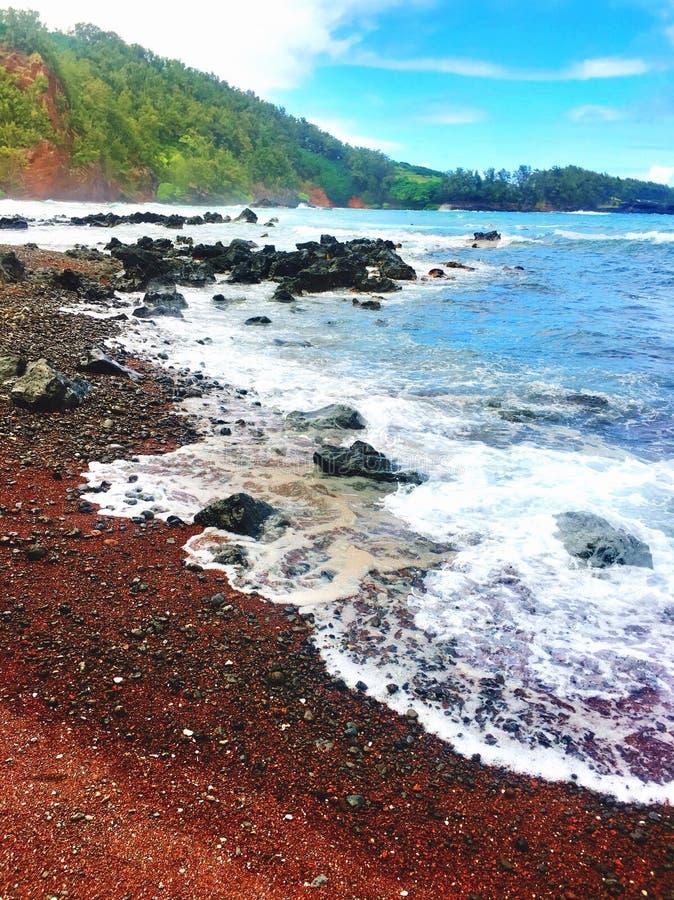 Rood zandstrand met lavarotsen op de kust in Maui Hawaï stock afbeeldingen
