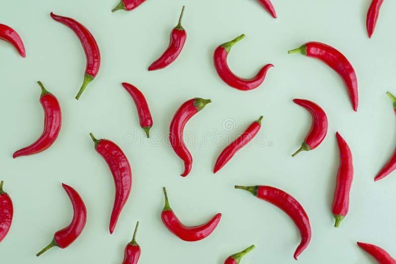 Roodgloeiende Spaanse peperspeper op groene achtergrond, flatlay kader, stock fotografie