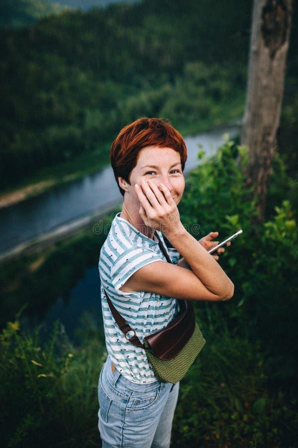 Roodharig hipstermeisje met een telefoon, tribunes tegen de achtergrond van de rivier Verwerking onder de film stock foto