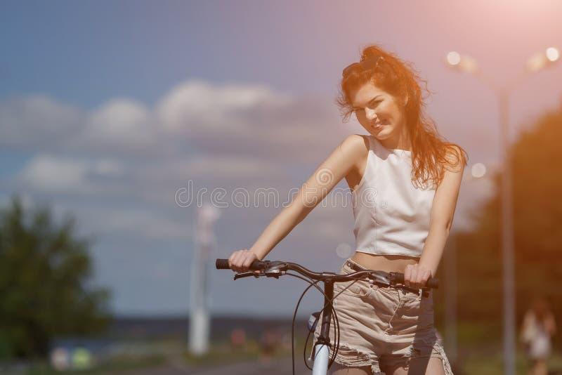Roodharig jong meisje in borrels en bovenkanten stellen die zich met fiets bevinden royalty-vrije stock afbeelding