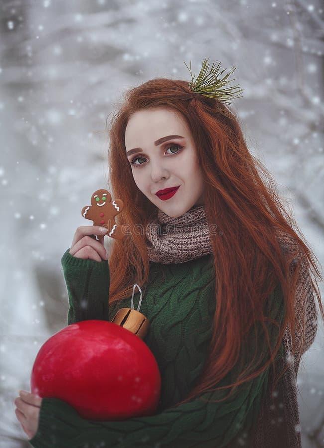 Roodharig langharig glimlachend meisje met een reusachtige Kerstmis rode bal die gemberkoekjes eten Een jonge vrouw met rood binn stock afbeeldingen