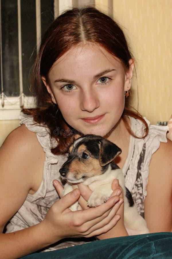 Roodharig meisje die een puppy Jack Russell houden royalty-vrije stock fotografie