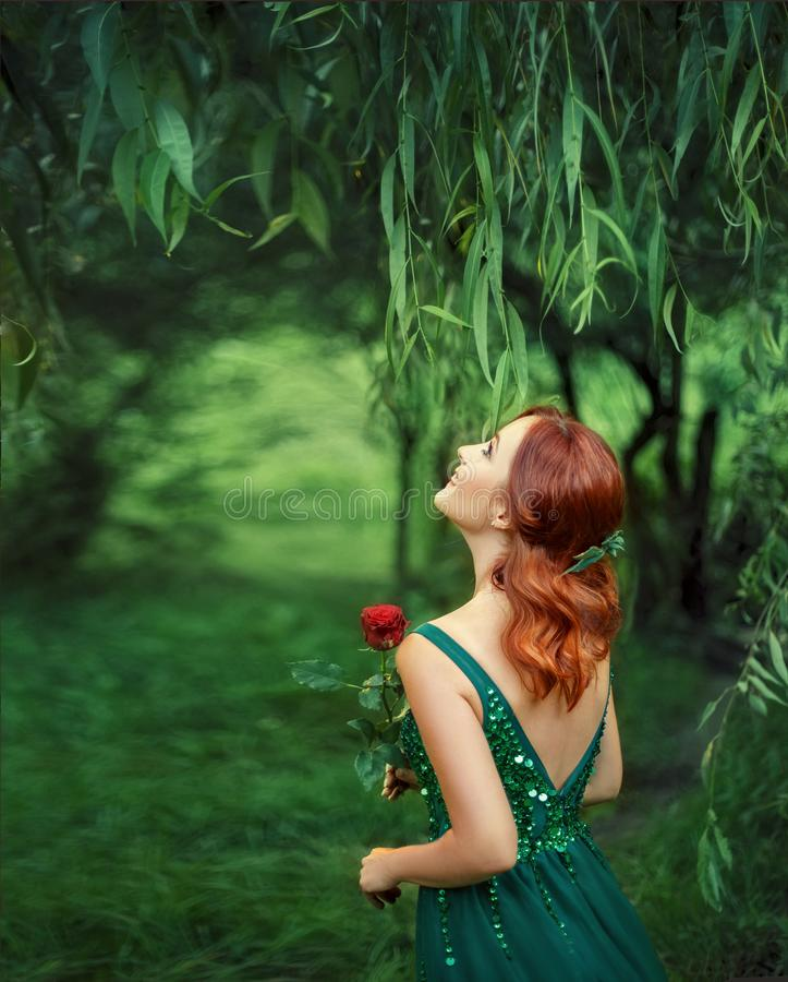 Roodharig meisje in een groene, smaragdgroene, luxueuze kleding met een open omhooggaand en rug die kijken lachen Foto van de rug stock afbeeldingen