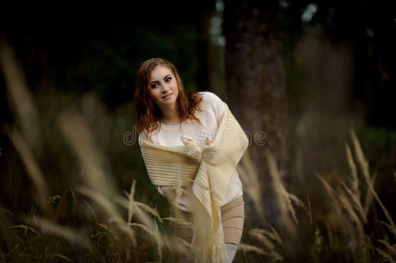 Roodharig meisje in lichte kleren tegen de achtergrond van de herfst bos en gele oren stock afbeelding
