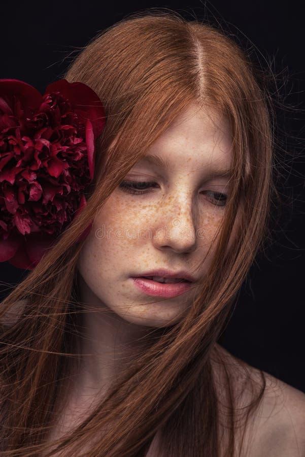 Roodharig meisje met rode bloem royalty-vrije stock afbeeldingen