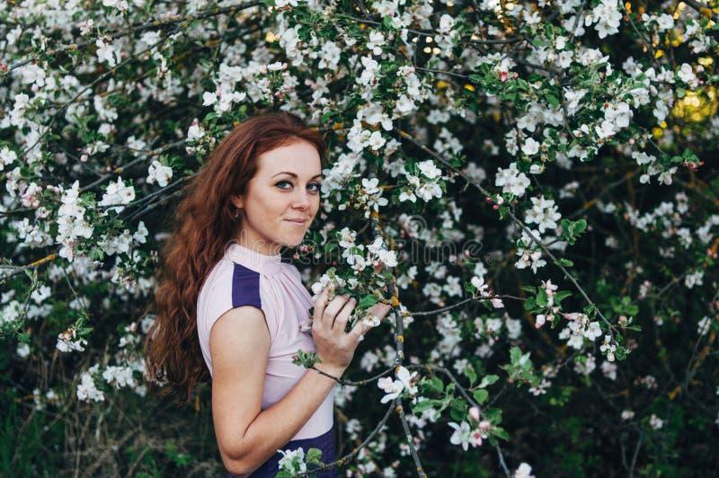 Roodharig meisje met sproeten dichtbij de appelboom royalty-vrije stock fotografie