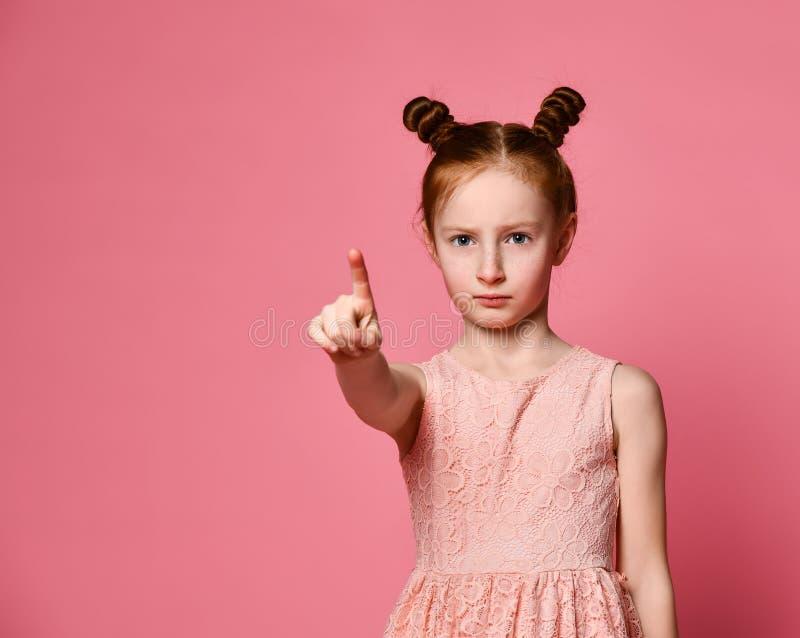 Roodharige ernstig meisje boven de roze muur die vol vertrouwen op u met een vinger richten stock fotografie