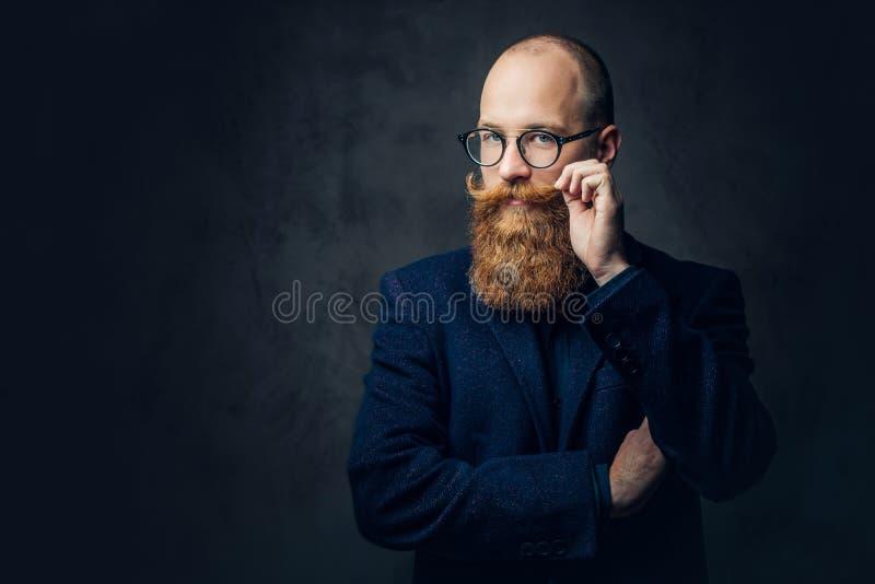 Roodharige gebaard mannetje in een kostuum stock fotografie