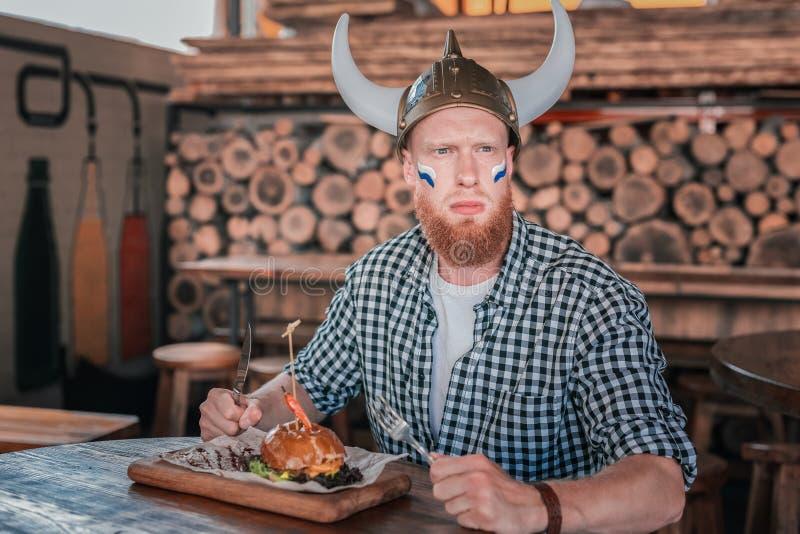 Roodharige gebaarde mens die Viking-hoed dragen die zijn hamburger eten royalty-vrije stock afbeeldingen