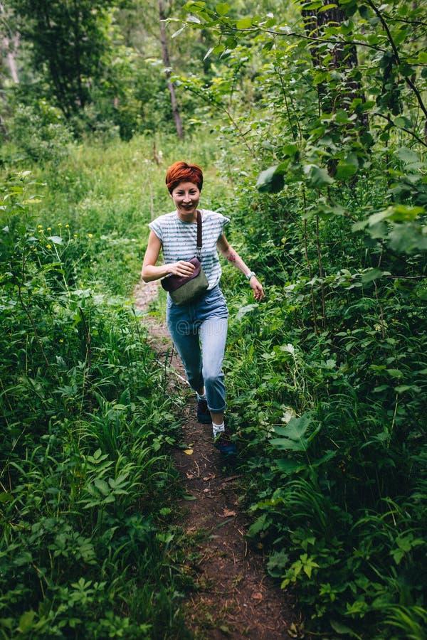 Roodharige hipster meisje die het de zomerbos doornemen royalty-vrije stock afbeeldingen